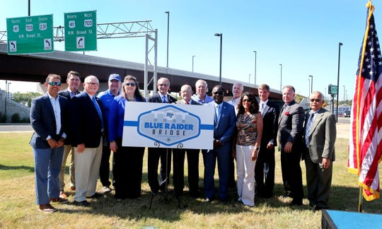 Several elected officials and MTSU President Sidney McPhee stand next to a sign and the bridge over Broad Street bridge which was officially named Blue Raider Bridge during a small ceremony on Thursday Sept. 5, 2019, in Murfreesboro.