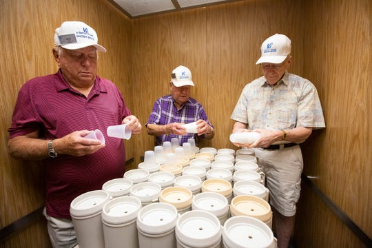 From left to right, Bob Hill, Tip Boerger, and Jon White pull out disposable cups in an elevator at Vi at Bentley Village on Thursday, September 5, 2019, in North Naples. There is a dozen of volunteer water boys, who are also the residents  at Bentley Village,  bring water to every residents at Bentley Care Center.