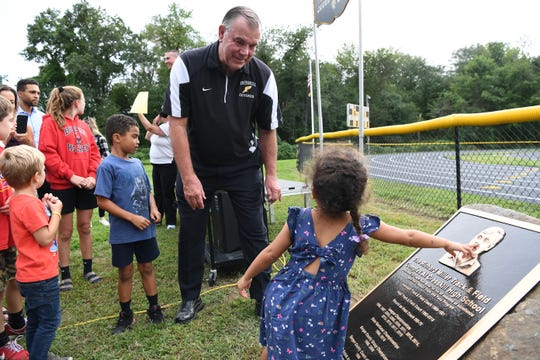 Rich Miller, a long-time Cresskill XC and track coach, looks on as his granddaughter Aria Robinson touches a plaque that was unveiled during a ceremony naming the track in his honor on Thursday, September 5, 2019.