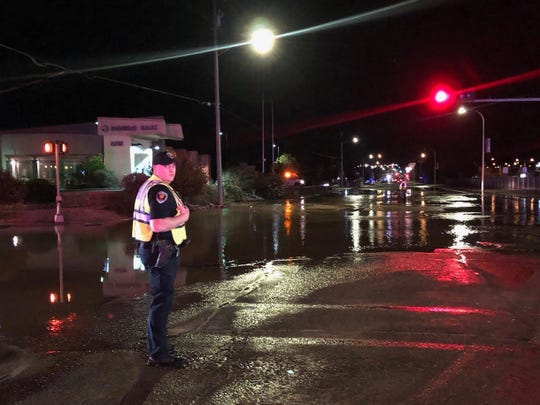 A Las Cruces police officer monitors El Paseo Road and University Avenue after a water main break flooded the intersection early Thursday, Sept. 5, 2019.