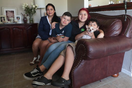 Lilia Ulloa, Juan Carlos Mendez, Gabriella Mendez Ulloa and Adrian Mendez sit on their living room couch in Riverside, Calif., on Tuesday, Sept. 3,  2019.