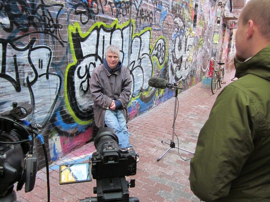 """Josh Hayes interviews a man experiencing homelessness for his documentary """"The Invisible Class."""""""