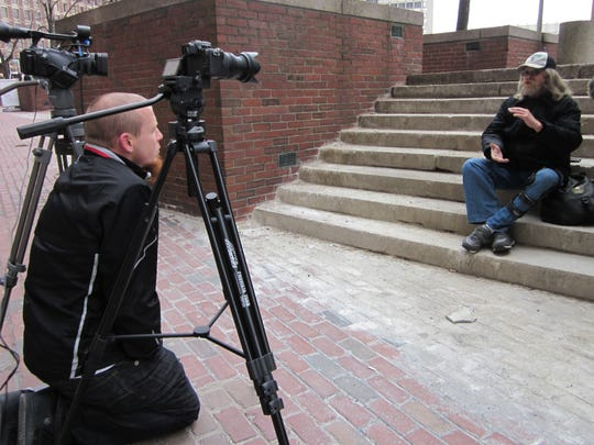 Josh Hayes interviews a man experiencing homelessness for his documentary The Invisible Class.