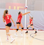 Lucy Kubas hits the return as teammates Jordyn Sapiro (1) and Mia Sherman (4) look on.