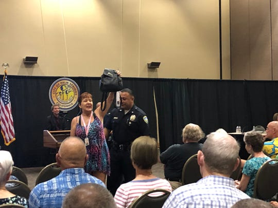 Angie Luntz gets escorted out of a community forum at the Palm Springs Convention Center on Wednesday, Sept. 4.