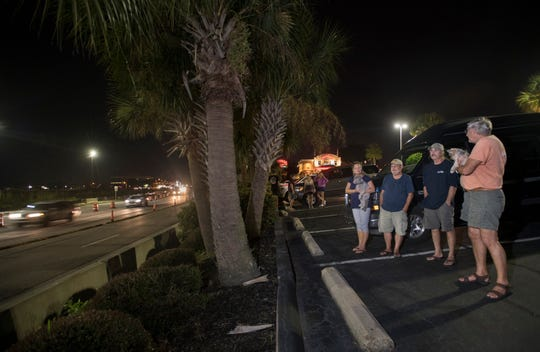 From right, John Cooper, Jerry Able, Rick Geist, and Karen Pfeifer were among a small group of people who gathered to watch traffic make its way over the new Pensacola Bay Bridge toward Gulf Breeze in Pensacola on Wednesday, September 4, 2019.