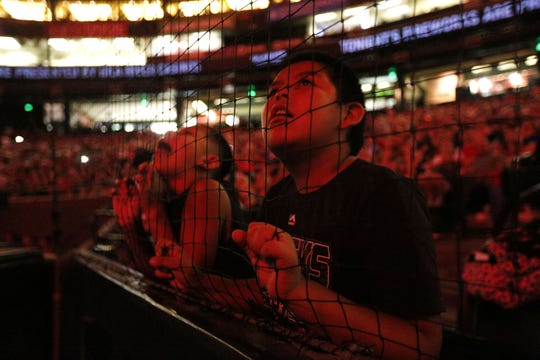 A fan watches fireworks through the netting behind home plate sat Chase Field. The Diamondbacks are planning to extend the netting in 2020.