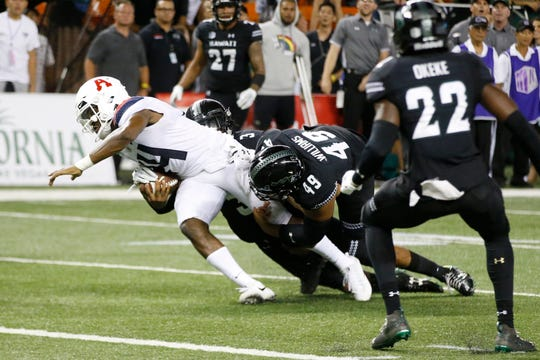 With no time left in the 4th quarter, Hawaii defensive back Kalen Hicks (3) and defensive lineman Manly Williams (49) tackle Arizona quarterback Khalil Tate (14) just short of the end zone during an NCAA college football game, Saturday, Aug. 24, 2019, in Honolulu.
