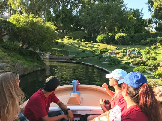 The Storybook Land Canal Boats float serenely through a miniature landscape.