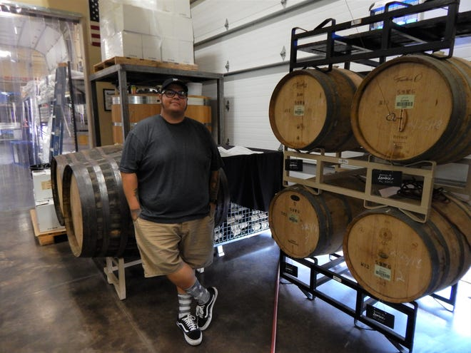 Co-founder Noel Garcia stands in front of barrels containing Cuvee Verdad, a sour beer passion project of his.