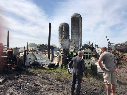A Pennsylvania State Police officer and fire marshal investigate the remains of a Myerstown barn that was destroyed in a fire Wednesday night.