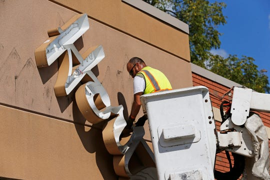 An employee of True Aerial Signs takes down a piece of Tim Hortons signage at the location along National Road West in Richmond on Thursday, Sept. 5, 2019.