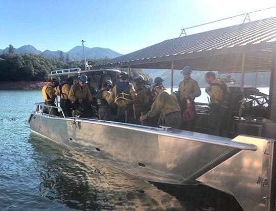 U.S. Forest Service firefighters return by boat after fighting the Green Fire near Green Mountain on the Pit River Arm of Shasta Lake. The fire on Aug. 28, 2019, burned nearly 1 acre following a lightning strike.
