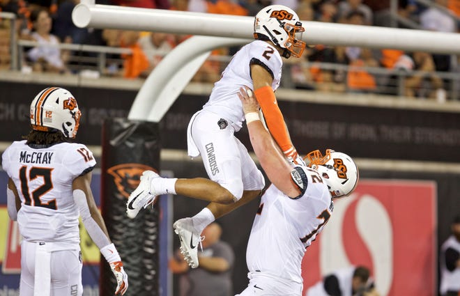 Oklahoma State Cowboys wide receiver Tylan Wallace and offensive lineman Johnny Wilson celebrate a touchdown during an NCAA football game on Friday, Aug. 30, 2019 in Corvallis, Ore.