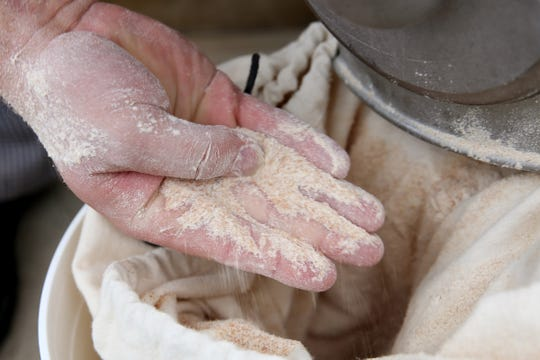 Mason Hinton, a baker, runs his hands through freshly milled wheat flour at the newly-opened Turner Baking Co. in Turner on Sep. 5, 2019.