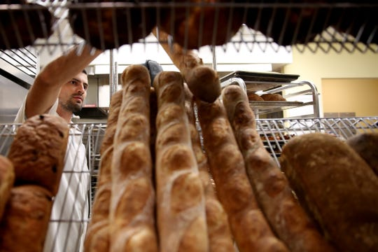 Aaron Brewer, the lead baker, lays out freshly baked baguettes at the newly-opened Turner Baking Co. in Turner on Sep. 5, 2019.