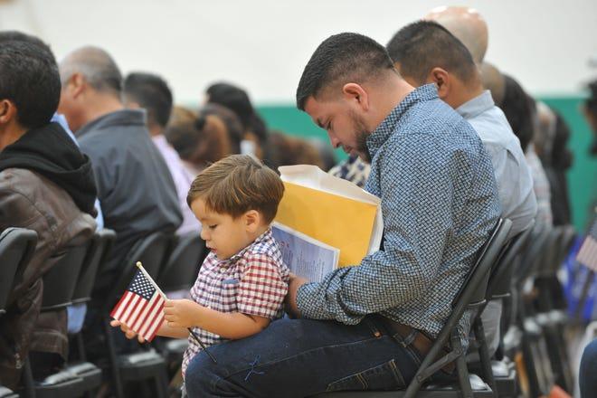 Héctor López, a la derecha, permanece sentado durante su ceremonia de naturalización para recibir la ciudadanía estadounidense mientras su hijo, Christopher, esta junto a él en Gonzales, California, el 5 de septiembre de 2019.