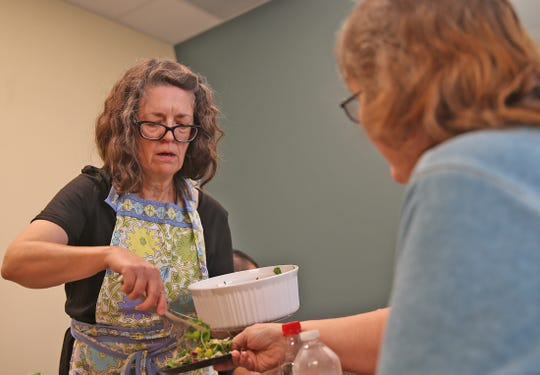 Marcia Merrell, left, serves up a salad to Navy vet Cynthia Pena, right, as part of a cooking class for veterans at the San Angelo VA clinic Tuesday, August 27, 2019.