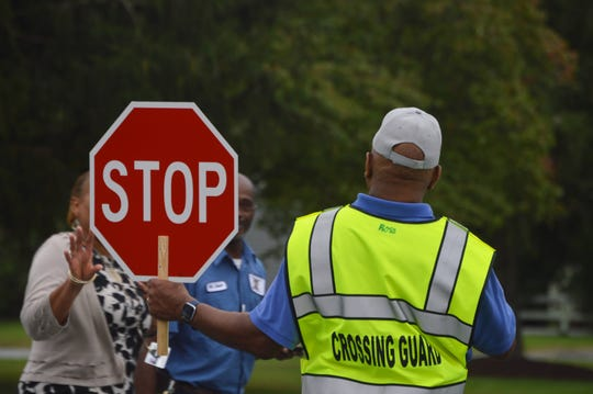Crossing guard Phillip Ross halts traffic so that school employees can cross Lake Street in front of Charles H. Chipman Elementary School in Salisbury, Maryland on Thursday, Sept. 5, 2019.