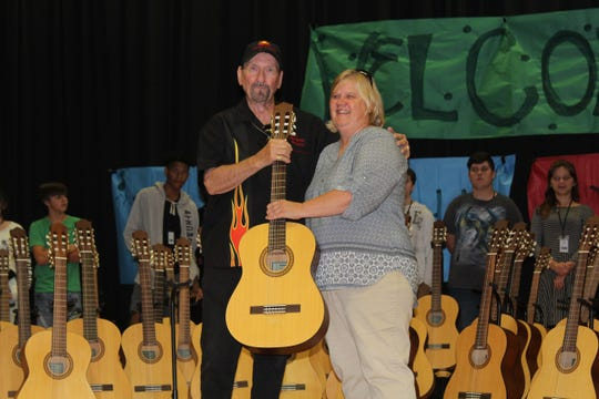 James Burton, Rock and Roll Hall of Famer, presents 60 guitars to music educator Vicki Kirkendall for student-lessons at North Caddo Elementary Middle School in Vivian.