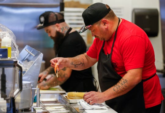 Cody Smith, right, puts together a Blackened shrimp banh mi sandwich topped with sambal aioli at the Lucky Tiger Sandwich Co., on Thursday, Sept. 5, 2019, in Springfield, Mo.