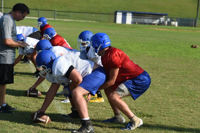 Fort Defiance head coach Dan Rolfe looks over his quarterbacks and centers during a practice earlier this summer.