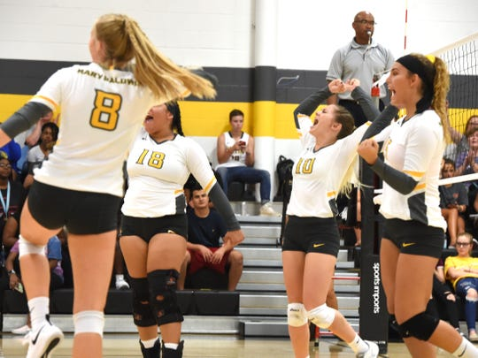 Deborah Black (10) celebrates a point with her Mary Baldwin teammates Wednesday night against Hollins.