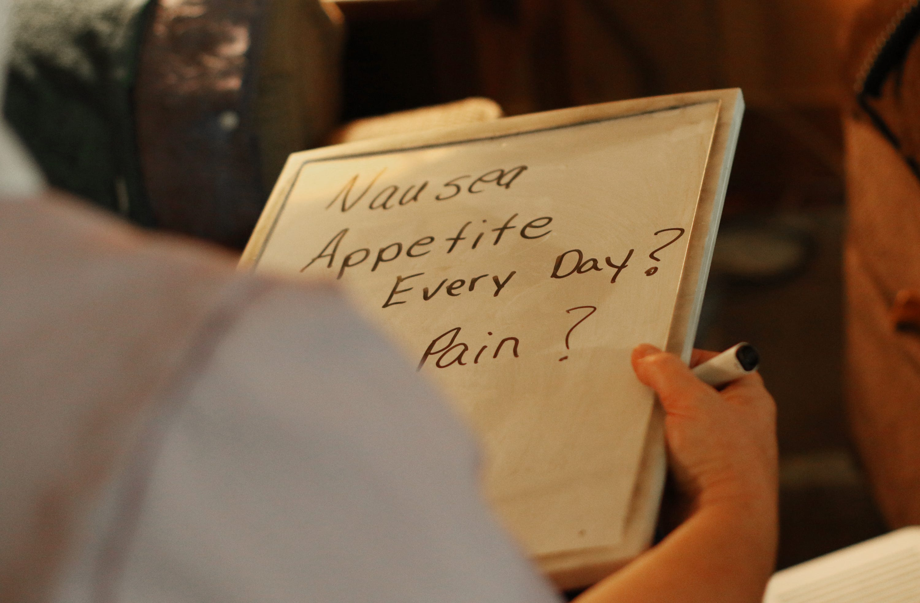 Laura Summy, a hospice nurse with Augusta Health, writes questions on a whiteboard for a patient who is hard of hearing at their home in Swoope on Aug. 27, 2019.