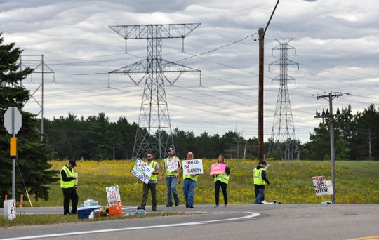 Security workers hold signs near an entrance to the Xcel Energy Monticello Nuclear Generating Plant Thursday, Sept. 5, 2019. The union workers have been locked out of the plant by their employer, G4s, since midnight Saturday.