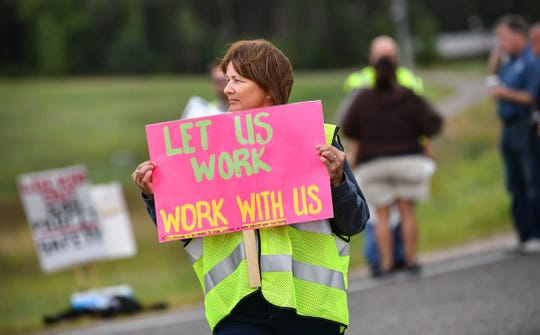 Heidi Proell holds a sign in support of her husband, 32-year security worker Tom Proell, outside an entrance to the Monticello nuclear power plant Thursday, Sept. 5, 2019.