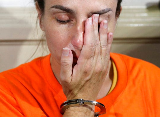 American Jennifer Erin Talbot from Ohio wipes her tears in handcuffs before the start of a press conference by the National Bureau of Investigation (NBI) in Manila, Philippines on Thursday, Sept. 5, 2019. The NBI said that the 43-year-old Talbot was arrested at the Ninoy Aquino International Airport yesterday for trying to bring out of the country a 6-day old Filipino baby without proper travel documents. (AP Photo/Aaron Favila)