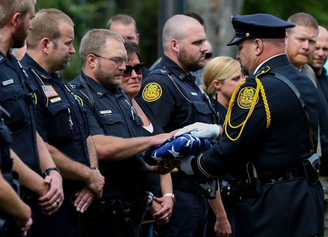 Officer J.D. Ballew and Kristin Ballew, his wife, are presented a folded United States flag during a memorial service for police dog Luna on Thursday, Sept. 5, 2019, at the Stevens Point Police Department in Stevens Point, Wis. Luna, who Ballew handled, died on Sept. 4 after a series of seizures progressed to multiple organ failure.