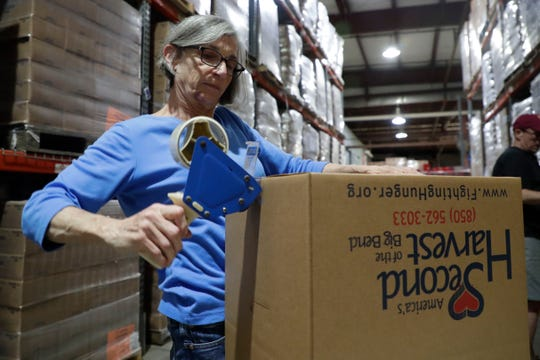 Chris Franzetti tapes together boxes as she volunteers with many others at Second Harvest Food Bank. The volunteers work as a team to package nonperishable food items to send to the Carolinas following the destruction from Hurricane Dorian.