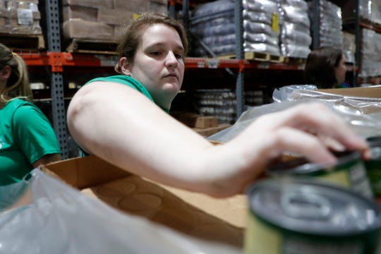 Amanda Leighty grabs canned soup to add to boxes of nonperishable food at Second Harvest Food Bank Wednesday, Sept. 4, 2019.