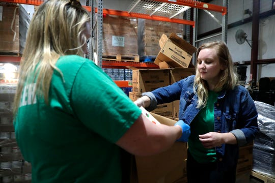 "At Second Harvest Food Bank, Lana Steele places a box of cereal in one of the 400 boxes of nonperishable food being sent to areas hardest hit by Hurricane Dorian. On Feb. 14, the food bank will host a ""Singles Sort"" service event."