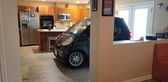 Jessica Eldridge shows her husband's solution to protecting his car from Hurricane Dorian. Patrick Eldridge parked his Smart car in their kitchen in Jacksonville.