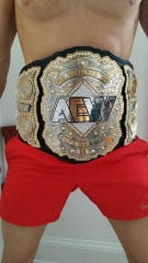 Frank Price posed for this torso-only photo of him wearing the AEW championship belt.