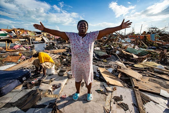 "Aliana Alexis, of Haiti, stands on the concrete slab of what is left of her home after destruction from Hurricane Dorian in an area called ""The Mud"" in Great Abaco Island, Bahamas, Thursday, Sept. 5, 2019, at Marsh Harbour."