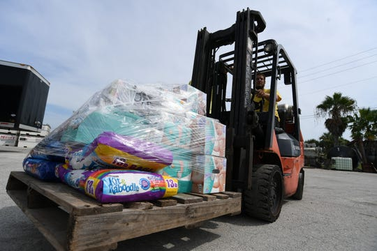 """Clayten Stewart, of Albury Brothers Boats, of West Palm Beach, moves a pallet of donated supplies to a staging area at McCulley Marine Services in Fort Pierce Thursday, Sept. 5, 2019, as volunteers from several companies collect relief supplies to be taken by barge on Friday to the Bahamas to help victims of Hurricane Dorian. """"I wouldn't do anything else but help out, if someone needs help we're going to help them,"""" Stewart said. """"I actually have a lot of family in the Bahamas. It's just the right thing to do."""""""