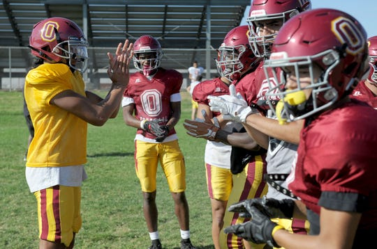 Jaden Jones huddles his offense during Wednesday's practice. Jones has taken over as the team's starting quarterback after the graduation of Vincent Walea.