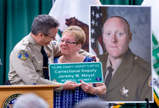 Tulare County Sheriff Mike Boudreaux, left, presents Judy Meyst a souvenir version of the highway sign honoring her son Deputy Jeremy Meyst during the unveiling to friends and family on Thursday, September 5, 2019. Deputy Meyst was killed in December of 2013 in a collision while transporting inmates on Ben Maddox Way south of Highway 198.