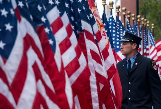An FDNY firefighter walks among flags at the FDNY Memorial Wall near the World Trade Center Sunday, Sept. 11, 2016, on the 15th anniversary of the attacks on the World Trade Center in New York.