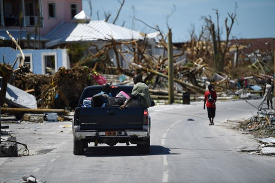 Residents pass damage caused by Hurricane Dorian on Sept. 5, 2019, in Marsh Harbour, Great Abaco Island in the Bahamas.