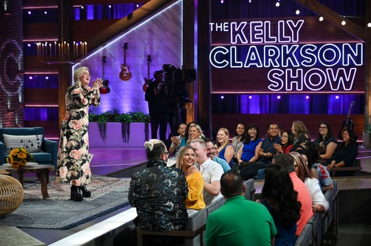 Kelly Clarkson takes the stage at her new talk show, which includes some audience seats positioned very close to the host and her guests.