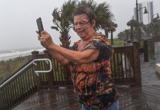 Anne Patterson gets a photo of the waves crashing near the boardwalk in Myrtle Beach, S.C., Sept. 5, 2019.