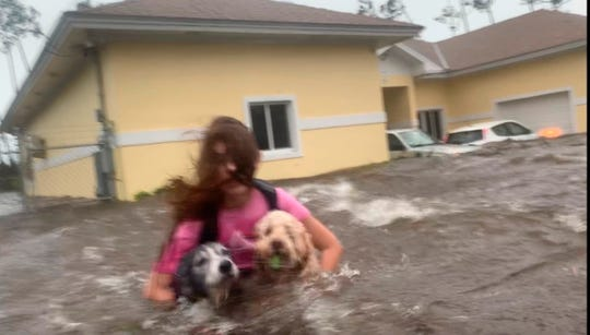 Julia Aylen wades through waist deep water carrying her pet dogs as she is rescued from her flooded home during Hurricane Dorian in Freeport, Bahamas, on Sept. 3, 2019.
