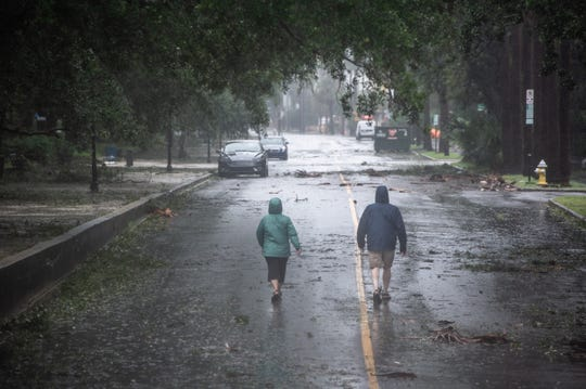 Two people walk down South Battery in Charleston, S.C., as Hurricane Dorian moves along the South Carolina coastline on Sept. 5, 2019.
