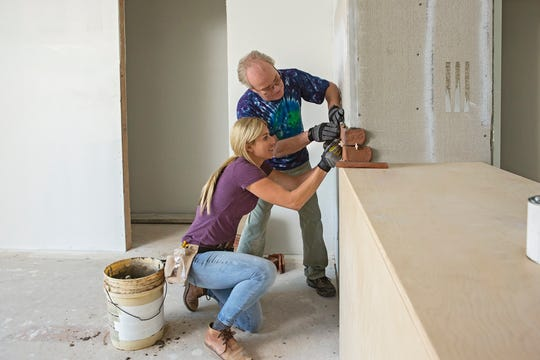 Jasmine Roth of HGTV's 'Hidden Potential, below, and Mike Lookinland, a star of 'The Brady Bunch,' apply brick facing as part of HGTV's 'A Very Brady Renovation.'