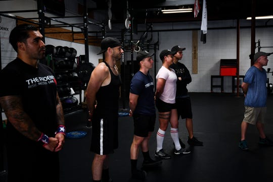 Members of The Phoenix sober active community listen to instructions before their cross-fit workout.
