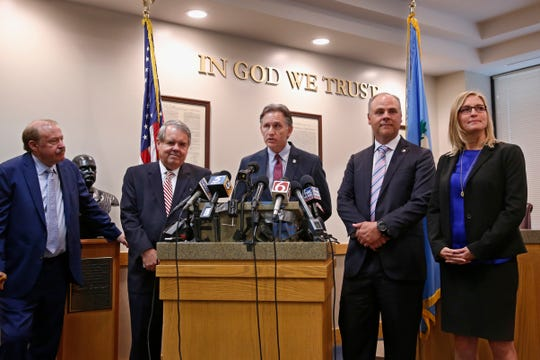 Oklahoma Attorney General Mike Hunter, center, answers a question during a news conference after the announcement of an opioid lawsuit decision in Norman, Okla., on  Aug. 26, 2019. Pictured from left are attorneys Reggie Whitten, Michael Burrage, Hunter, attorney Brad Beckworth and Terri White, Commissioner, Oklahoma Department of Mental Health and Substance Abuse Services.